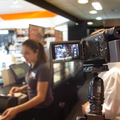 POS user at till in gas station is filmed for user research observation study